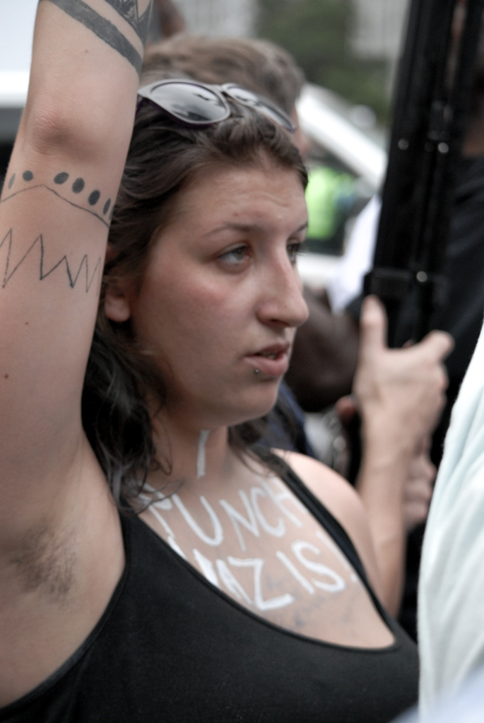 "A girl raises her arm with ""I punch Nazis"" written on her chest in silver glitter during protest activity in Washington D.C. on Aug. 12, 2018."