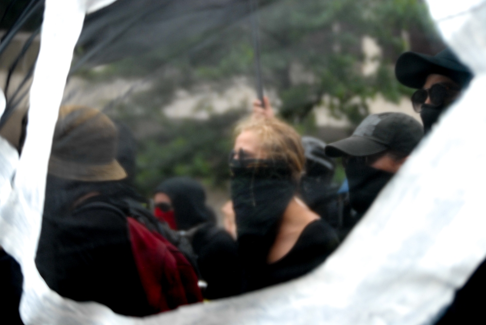 A masked anti-fascist activist shot through a protest sign during a march against Unite the Right 2 in Washington D.C. on Aug. 12, 2018.
