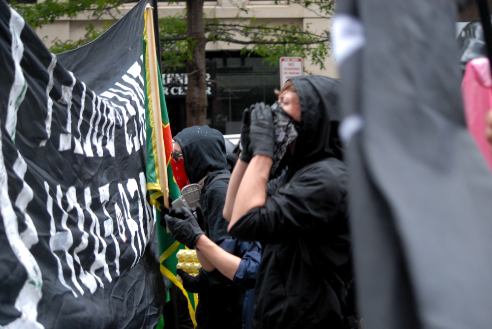 A masked anti-fascist activist yells during protest activity in Washington D.C. on Aug. 12, 2018.