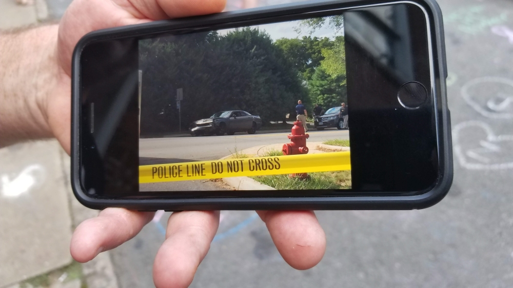 A man shows video on his phone of when  Heather Heyer was killed in Charlottesville by a white supremacist the year before.